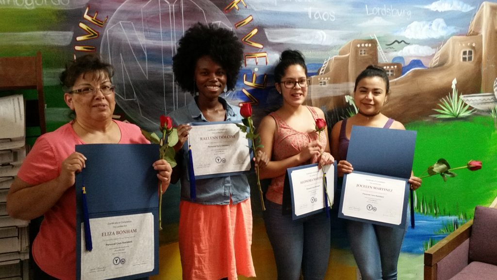 Four graduates from the Personal Care Aide program display their diplomas.