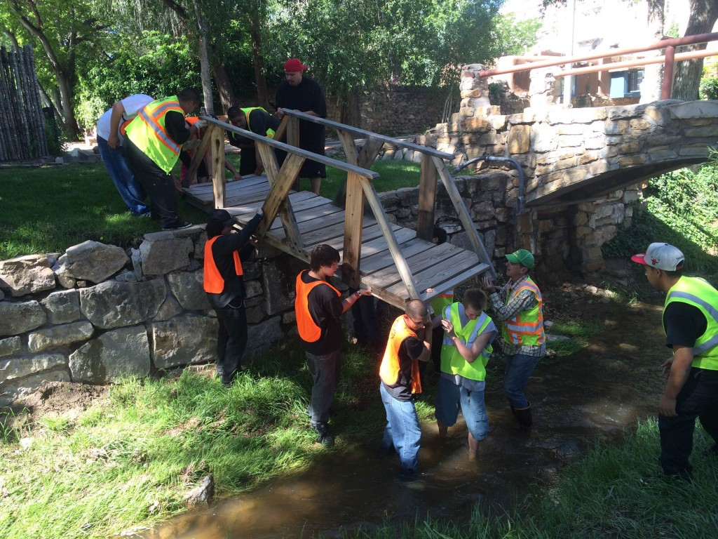 ¡YouthWorks! river restoration crew installs a bridge across the Santa Fe River.