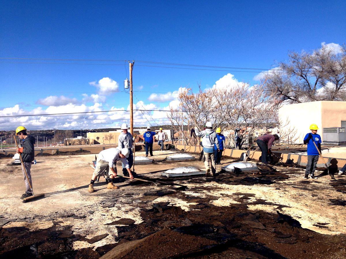 The YouthBuild crew removes the old roof from the ¡YouthWorks! building.