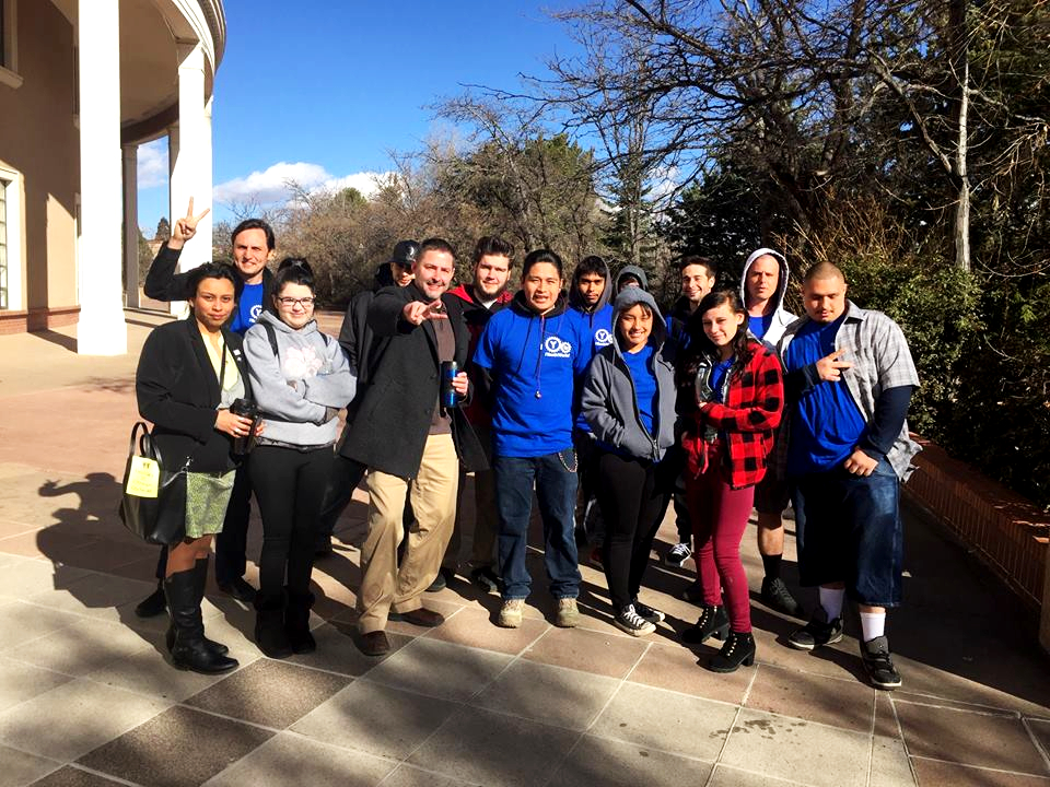 A crew from ¡YouthWorks! poses for a photo outside the New Mexico State Capitol..