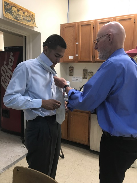 Juan gets a lesson in how to tie a tie.
